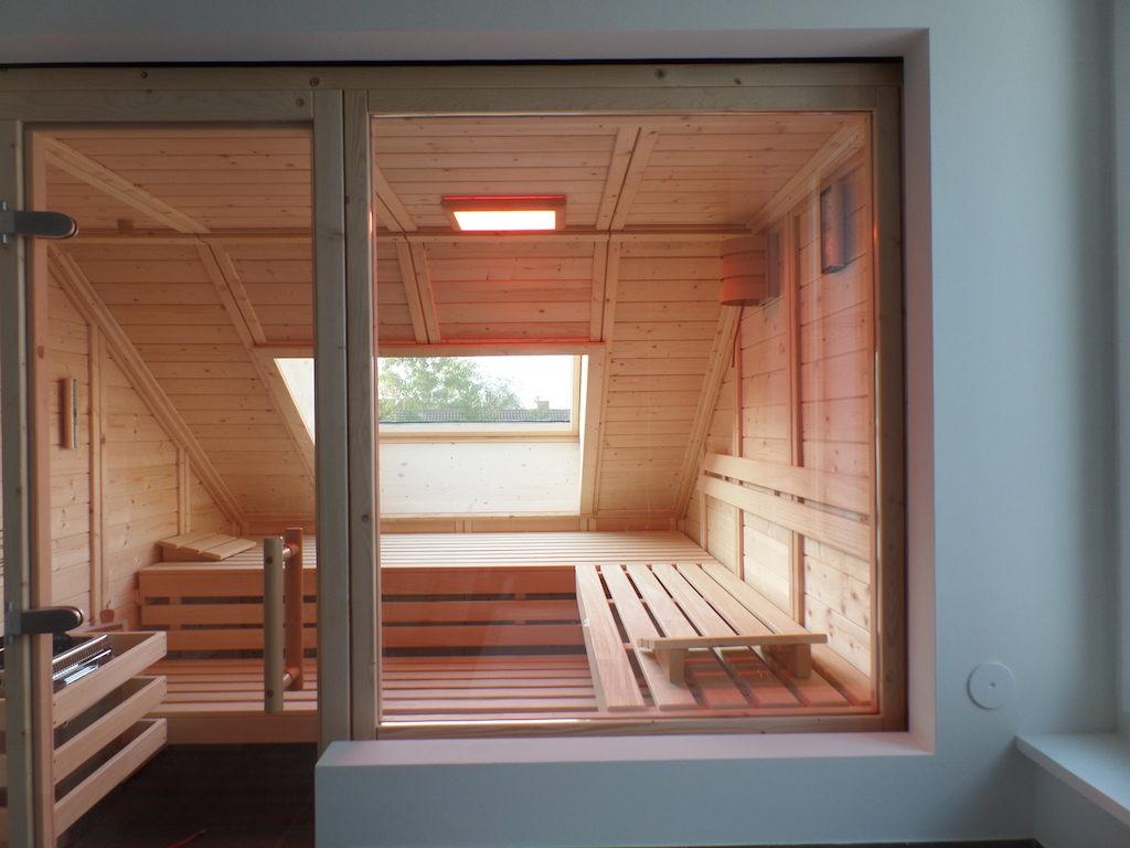 Vielfältig kombiniert: Massivholsauna unter Dachschräge mit integriertem Fenster und Design-Glaselementen